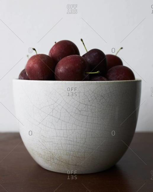 Close-up of a crackle glazed bowl of fresh plums