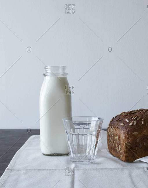 Bottle of milk with glass and loaf of whole-grain bread