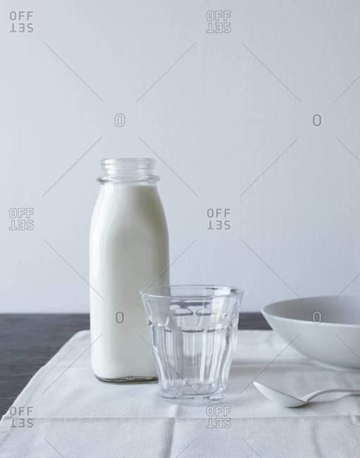 Still life of bottle of milk, glass and ceramic bowl