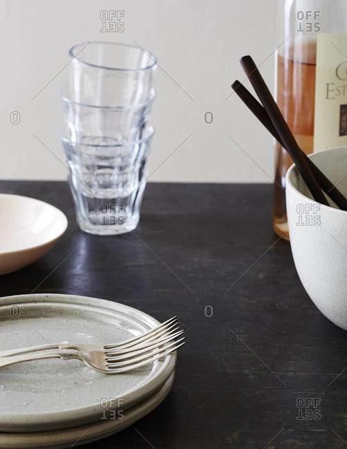 Kitchen table with dishes and glassware with bottle of wine