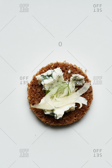 Round bread crackers topped with gorgonzola, fennel and dill