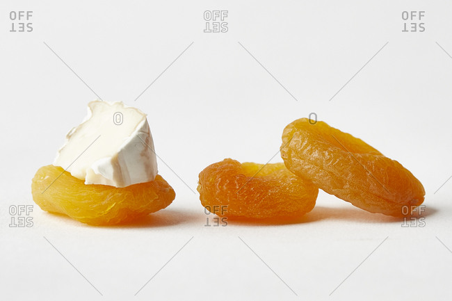 Dried apricots, one topped with brie