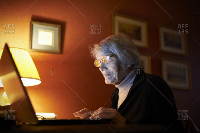 Senior Woman At Home Using Laptop Computer At Desk