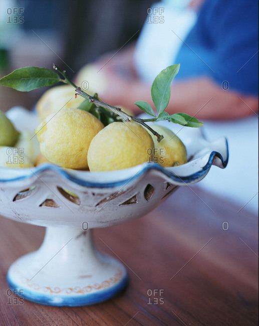 Pottery bowl of lemons on table