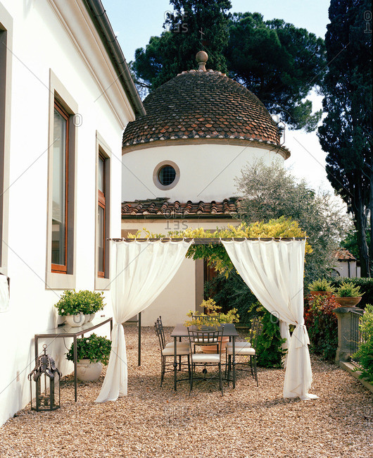 Dining table framed by curtains in courtyard of domed stucco building