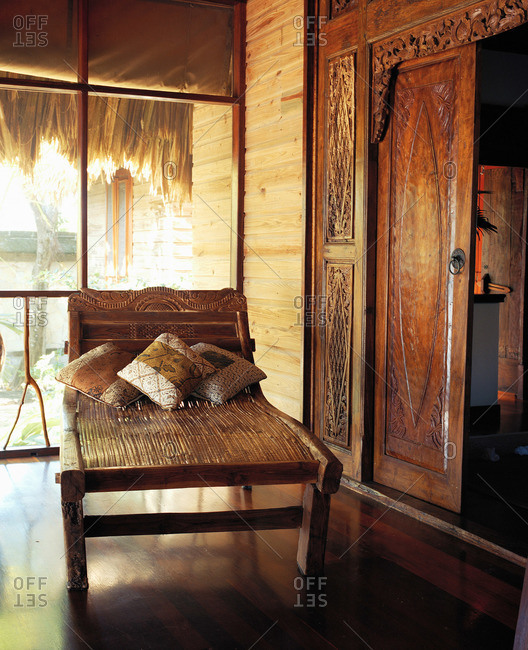 Rustic bamboo and carved wood chaise lounge on screened porch