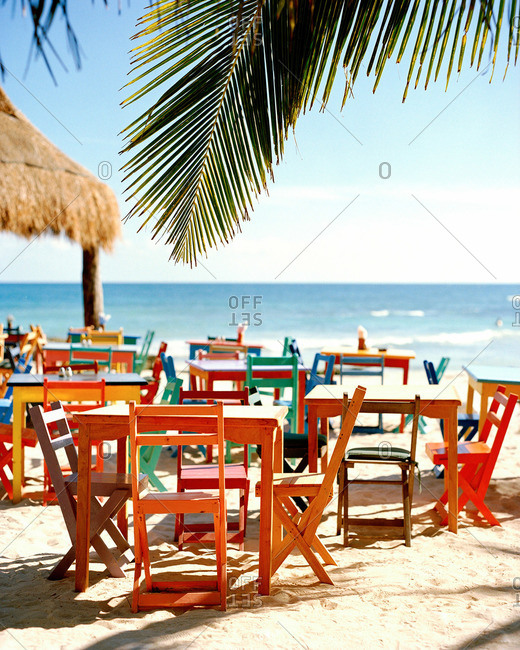 Colorful wooden tables and chairs at a beach restaurant