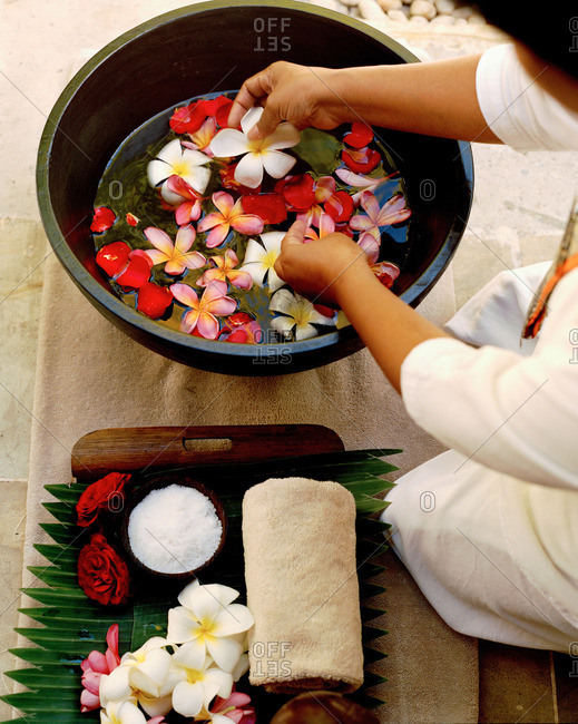 Woman placing flowers in bowl of water for spa treatment