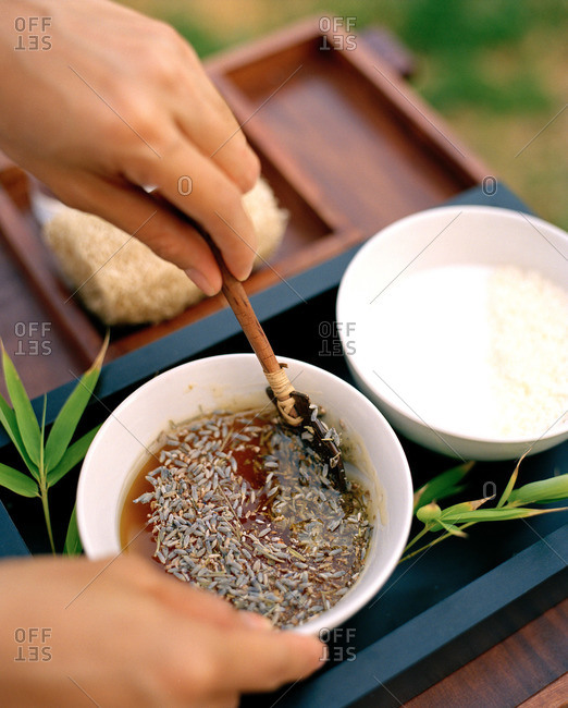 Dried lavender being mixed into oil for spa treatment