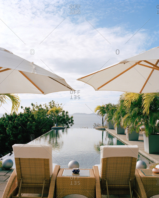 Two woven lounge chairs under umbrellas at end of pool