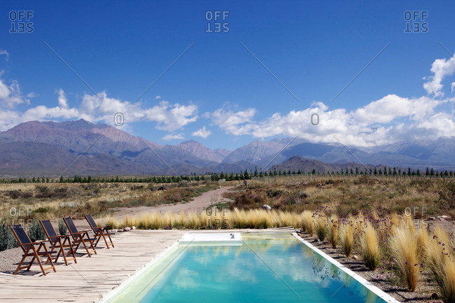 Chairs lined up next to pool in open field