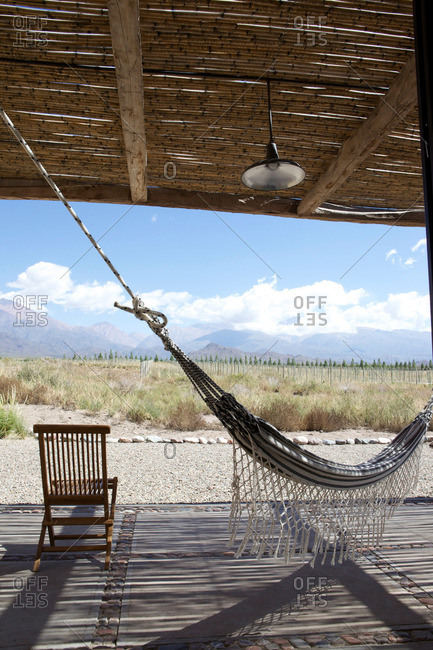 Hammock and chair in bamboo pavilion in field with mountains in distance