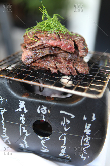 Meat being grilled on portable hibachi