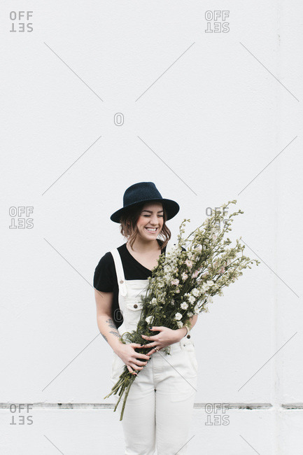 Laughing woman in black hat with white overalls holds white flowers against white wall