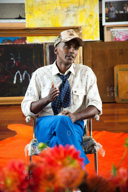 New York City - August 21, 2012: Chef Marcus Samuelsson sitting in chair surrounded by paintings in his colorful living room