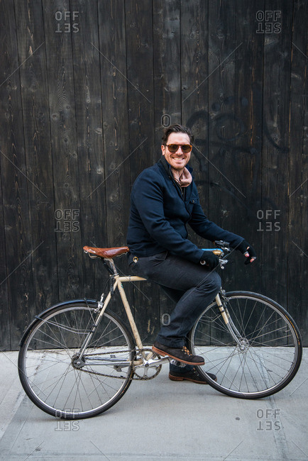 New York City - August 19, 2012: Portrait of Chef Seamus Mullen posing on bicycle against wooden fence
