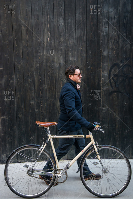 New York City - August 19, 2012: Stylish man walking with bicycle on sidewalk in front of wooden fence
