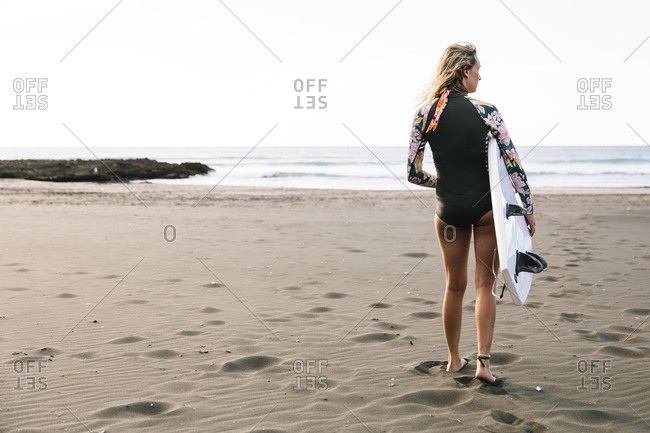 Piha Beach, Auckland, New Zealand - January 7, 2016: Woman standing on a beach holding her surfboard