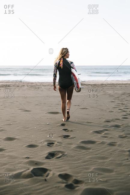 Piha Beach, Auckland, New Zealand - January 7, 2016: Woman carrying her surfboard across a beach