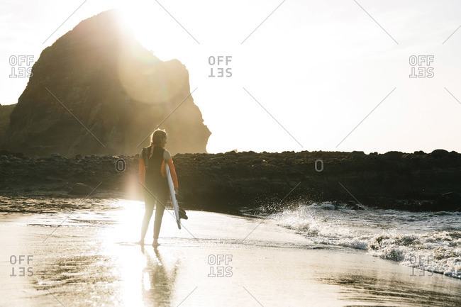 Piha Beach, Auckland, New Zealand - January 7, 2016: Woman standing on a rocky coast holding her surfboard