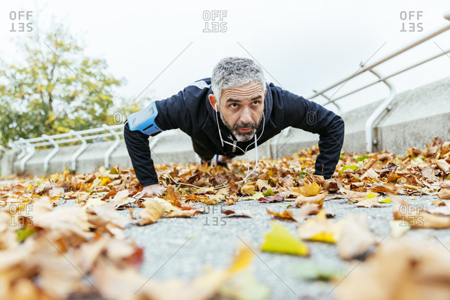 Man doing pushups surrounded by autumn leaves