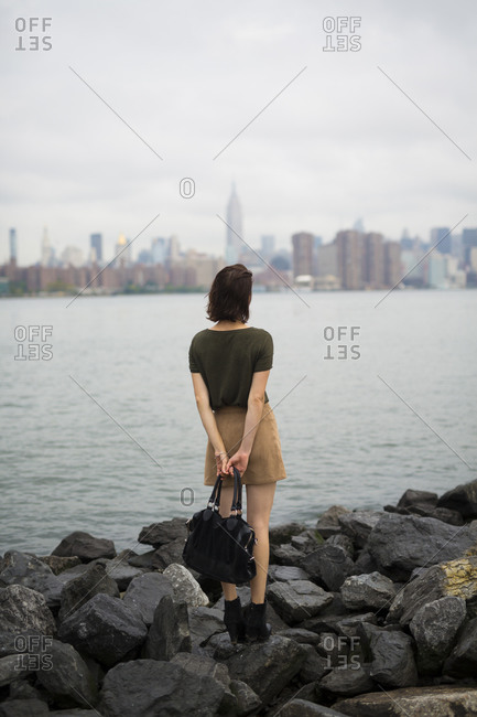 Young woman looking to Manhattan skyline from Williamsburg bank