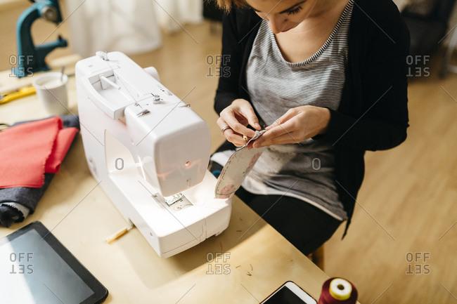 Young fashion designer checking a seam