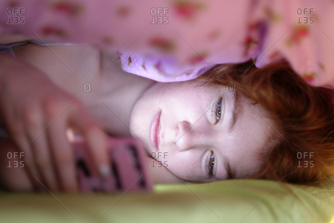 Portrait of girl lying under blanket in bed looking at her smartphone