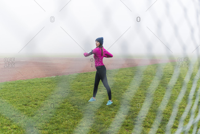 Young woman doing workout on a grass behind mesh wire fence