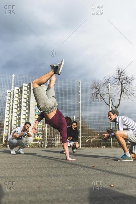 Friends cheering encourage a break dancer