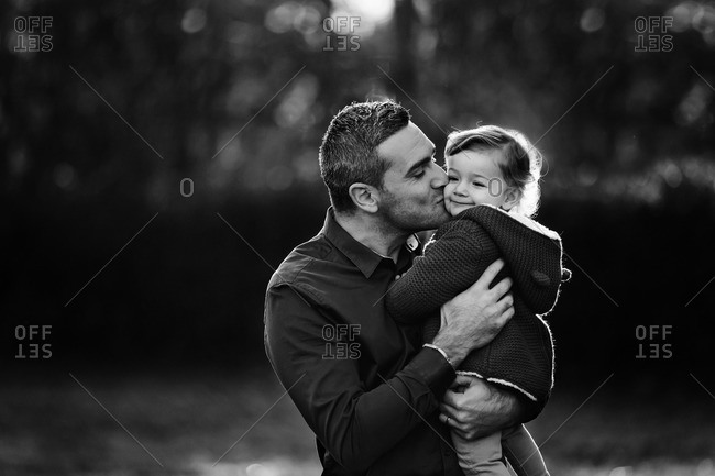 Dad tenderly kissing daughter outside