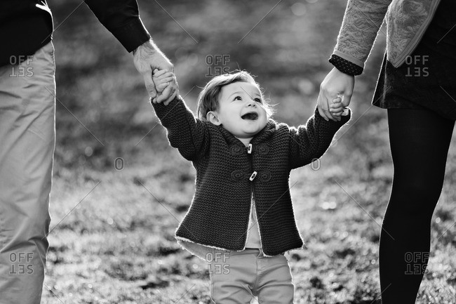 Happy toddler girl holding parents' hands