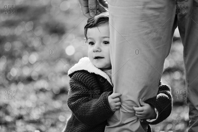 Toddler girl clinging to man's leg