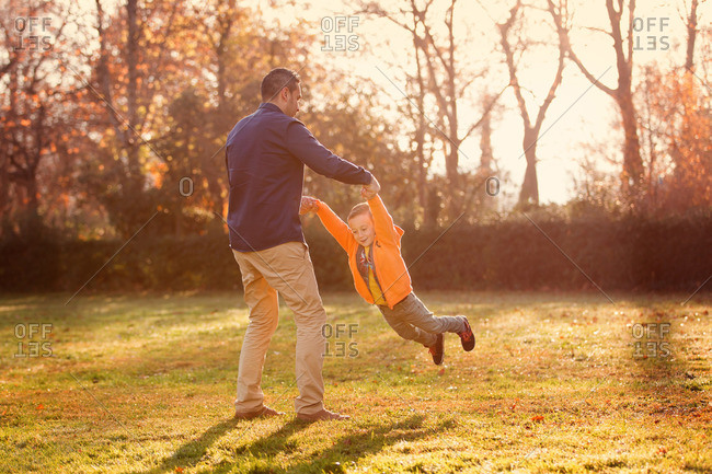 Dad swinging child in rural setting