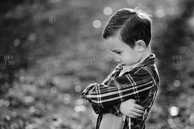 Pouting boy in rural setting