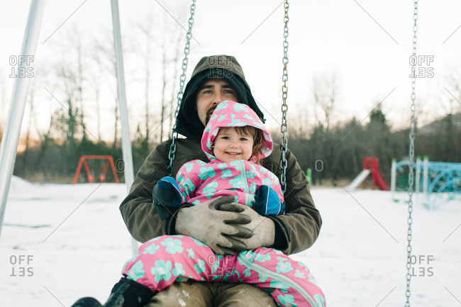 Little girl and father on a swingset in the snow