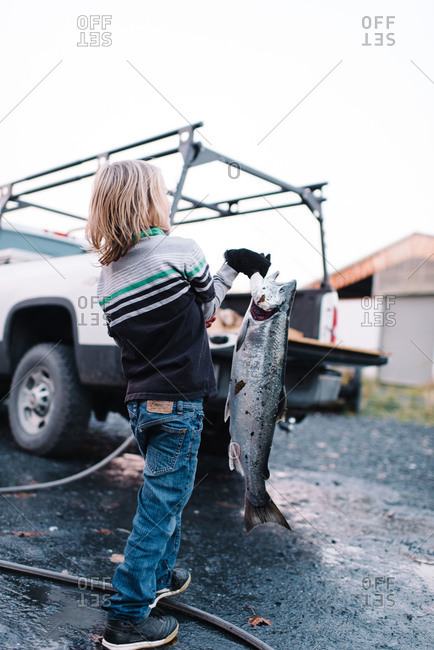 Little boy carrying a fresh-caught fish to a truck