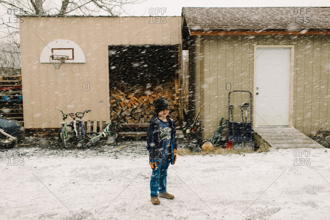 Little boy standing outside in front of a shed in snowfall