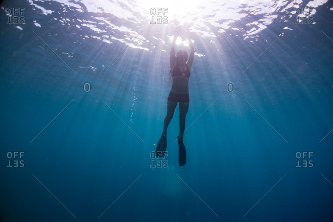 Young woman swimming toward the ocean surface as sunbeams enter the water