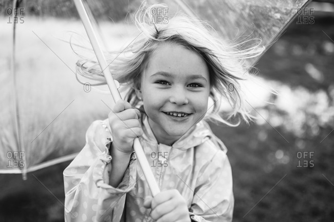 Little girl in a raincoat holding an umbrella