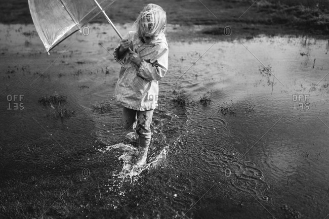 Little girl splashing in a large puddle