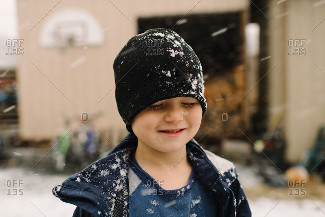 Boy squinting against windy snow