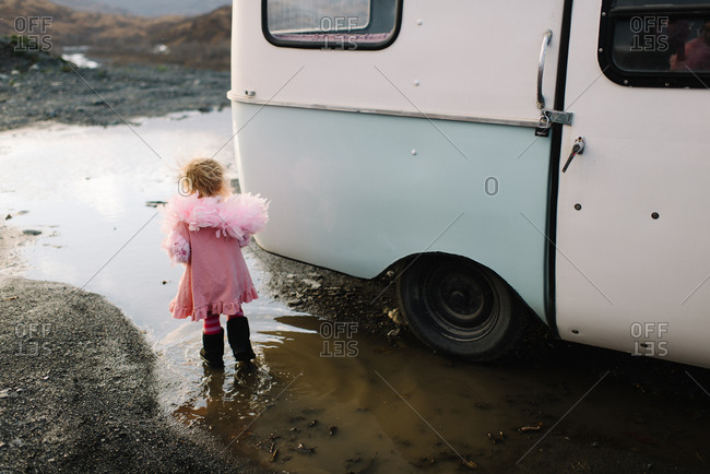 Girl standing in mud puddle next to a camper van