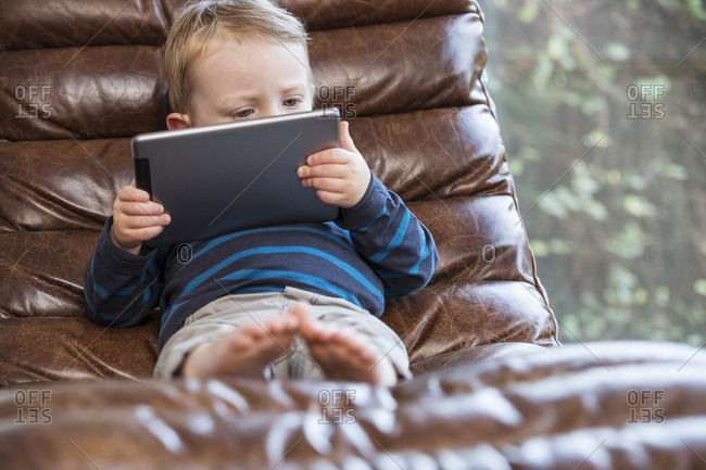 Little boy in a leather chair looking at a tablet