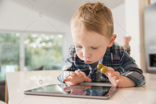 Little boy with olives on his fingers looking at a tablet