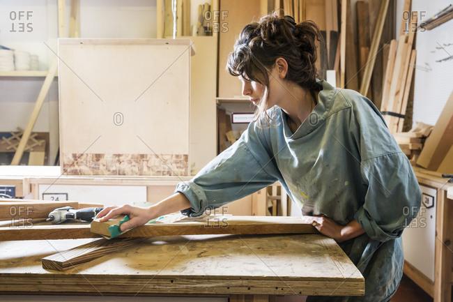 Woman sanding a board in a woodworking shop