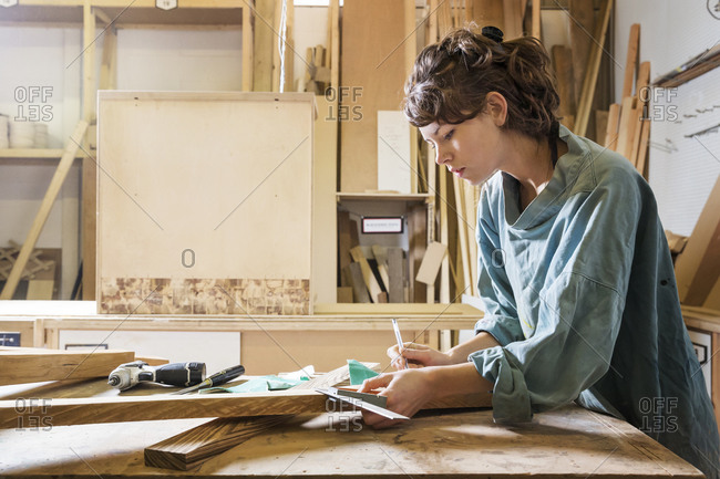 Woman measuring a board in a woodworking shop