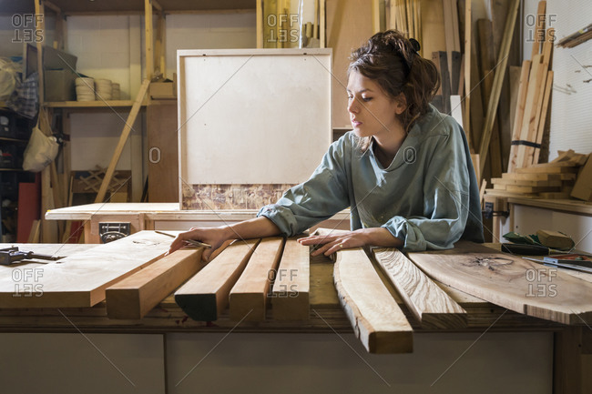 Young woman measuring pieces of wood in a workshop