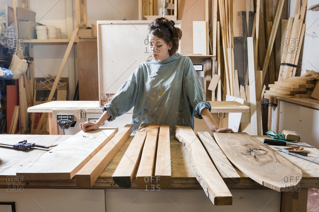 Young woman in a workshop inspecting pieces of wood