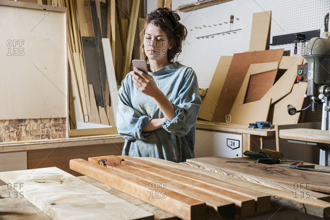 Young woman in a woodworking shop on her cellphone